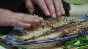 Équipez les mains épluchant la peau de la truite brune frite d'Ohrid de lac clips vidéos