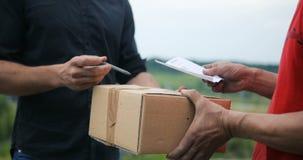 Équipez les mains acceptant une livraison des boîtes du livreur, messager de fond de champ de campagne banque de vidéos