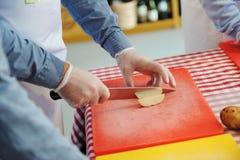 Équipez les mains coupant en tranches la pomme de terre fraîche sur le hachoir Image stock