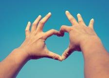 Équipez les mains dans l'amour de forme de forme de coeur sur le ciel Photographie stock libre de droits
