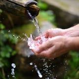 Équipez les mains de lavage dans l'eau fraîche, froide, potable Photo libre de droits