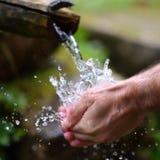 Équipez les mains de lavage dans l'eau fraîche, froide, potable Photographie stock libre de droits