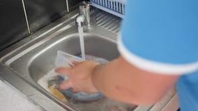 Équipez les mains du ` s lavant des plats dans un évier de cuisine banque de vidéos