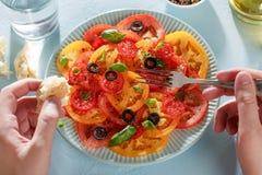 Équipez les mains du ` s mangeant le carpaccio fait maison de tomate avec du pain et la fourchette images stock