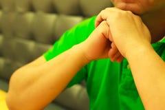Équipez les mains du ` s serrées en position augmentée, concept de langage du corps photo libre de droits