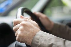 Équipez les mains du ` s sur la roue d'une voiture Photo stock