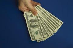 Équipez les mains du ` s tenant des dollars sur le fond bleu-foncé Photos libres de droits
