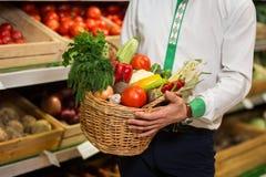 Équipez les mains du ` s tenant un panier des légumes moissonnent sur le marché image stock
