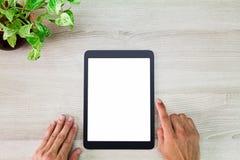 Équipez les mains du ` s utilisant la tablette blanche vide d'écran avec le pot de plante verte sur la table en bois Photo libre de droits