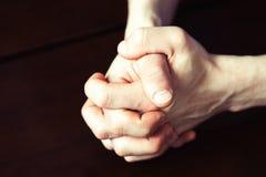 Équipez les mains fortes du ` s étreintes sur la table en bois foncée photos libres de droits