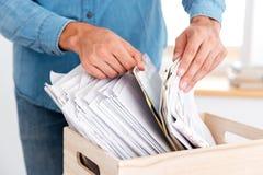 Équipez les mains recherchant des documents dans la pile de dossiers Image stock