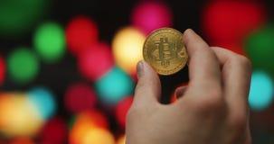 Équipez les mains tenant de cryptos pièces de monnaie d'or de la devise BTC Bitcoin sur un fond coloré brouillé banque de vidéos