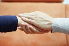 Équipez les mains tenant la main de femme des deux côtés compassion Photo stock