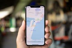 Équipez les mains tenant le service cartographique AP d'application de l'iPhone X images stock