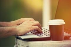 Équipez les mains utilisant l'ordinateur portable et le café pour aller plan rapproché extérieur Image stock