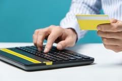 Équipez les mains utilisant le clavier et tenir la carte de crédit avec le media social en tant que concept en ligne d'achats sur Photographie stock