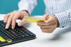 Équipez les mains utilisant le clavier et tenir la carte de crédit avec le media social en tant que concept en ligne d'achats sur Photo libre de droits
