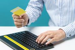 Équipez les mains utilisant le clavier et tenir la carte de crédit avec le media social en tant que concept en ligne d'achats sur Image stock