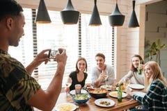 Équipez les photos debout et parlantes des amis à l'aide du téléphone portable Photos stock