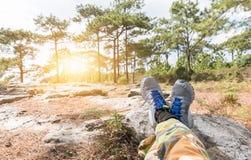 Équipez les pieds dans des espadrilles détendant sur la roche Images libres de droits