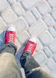 Équipez les pieds dans des espadrilles rouges sur la route pavée en cailloutis Photos libres de droits