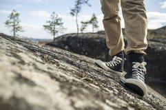 Équipez les pieds du ` s dans des espadrilles noires sur les roches Image libre de droits