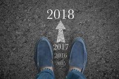 Équipez les pieds sur la route goudronnée avec la nouvelle année 2018 de début Images stock