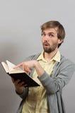 Équipez les points un doigt dans un livre intéressant Photographie stock libre de droits