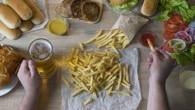 Équipez les pommes frites de versement en sauce et bière potable, consommation malsaine, calories banque de vidéos