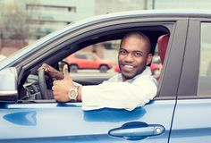 Équipez les pouces de représentation de sourire heureux de conducteur conduisant la voiture de bleu de sport Photographie stock libre de droits