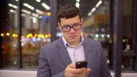 Équipez les sms textotant utilisant l'APP au téléphone intelligent la nuit dans la ville Jeune homme beau d'affaires employant le clips vidéos