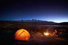 Équipez les touristes s'asseyant dans la tente lumineuse près du feu de camp Photographie stock libre de droits