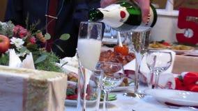 Équipez les verres de versement de champagne pour la table de vacances banque de vidéos