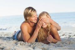 Équipez les yeux d'amies de bâche se trouvant sur la plage Photos stock