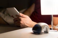 Équipez lire le livre électronique ou à l'aide du comprimé dans le lit photos libres de droits