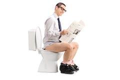 Équipez lire un journal posé sur une toilette Images stock