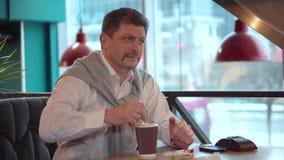 Équipez mûr dans une chemise blanche avec du sucre d'émois de chandail avec un bâton dans le café nouvellement fabriqué de matin banque de vidéos