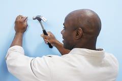 Équipez marteler le clou dans le mur photo libre de droits