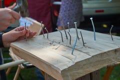 Équipez marteler un clou dans un bloc de bois dur Images stock