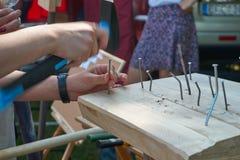 Équipez marteler un clou dans un bloc de bois dur Images libres de droits