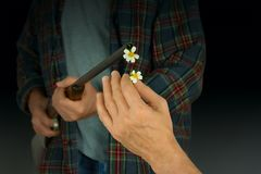 Équipez mettre des fleurs dans le baril de l'arme à feu représentant choisissant la paix au-dessus de la violence image libre de droits