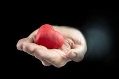 Équipez mettre en forme de tasse un coeur rouge dans sa main Photos stock