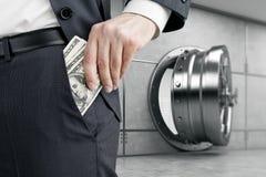 Équipez mettre l'argent dans la poche près de la chambre forte Image stock