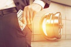 Équipez mettre l'argent dans la poche près de la chambre forte ensoleillée Image libre de droits