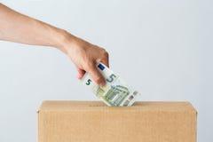 Équipez mettre l'euro argent dans la boîte de donation Photos stock