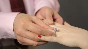 Équipez mettre le bel anneau argenté sur la main de la femme, proposition de mariage, engagement banque de vidéos