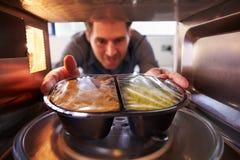Équipez mettre le dîner de TV dans la micro-onde Oven To Cook photo stock