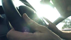 Équipez mettre ses mains sur le volant de voiture contre le soleil de flambage, la vidéo 4K clips vidéos
