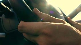 Équipez mettre ses mains sur le volant en cuir contre le soleil de flambage, couleurs chaudes vidéo 4K banque de vidéos