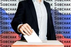 Équipez mettre un vote dans une boîte de vote Élections de démocratie dans le concept de la Russie Sobchak Photo libre de droits